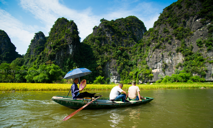 Foreign tourists take a boat ride on Ngo Dong River in Tam Coc-Bich Dong