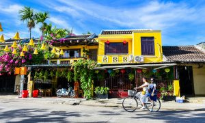 Tourists ride their bicycles in the ancient town of Hoi An